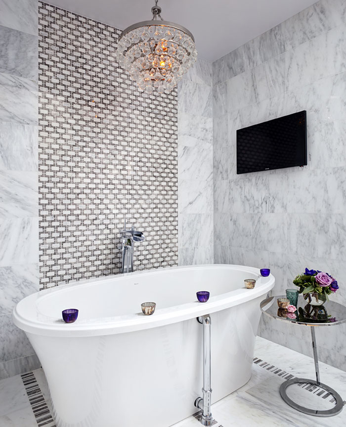 Crystal chandelier and tiled feature wall add impact to the marble-clad ensuite.
