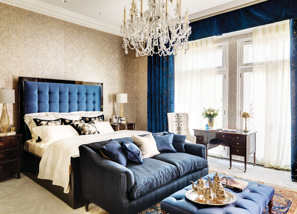 Master bedroom: Blue silk covers the head and footboard of a Rosewood Simonetto bed. Neaumont and Fletcher bespoke blue silk drapes, threaded in silver and Swarovski crystals, finish the windows.
