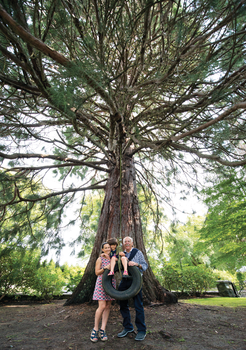 Margot Keate-West and Richard Keate, architectural designers, with Eloise West, under the giant sequoia in the front yard of an ancestral Shaughnessy home. The tree was planted in honour of Richard's great grandfather.