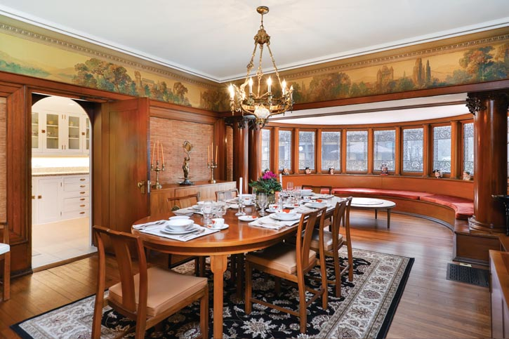 A curving bank of windows extends and completes Wright's intricate formal dining room design. He likely drew the leaded glass patterns himself — he was famous for giving his projects all of their finishing touches. The exact same window designs appear in Wright's personal residence.