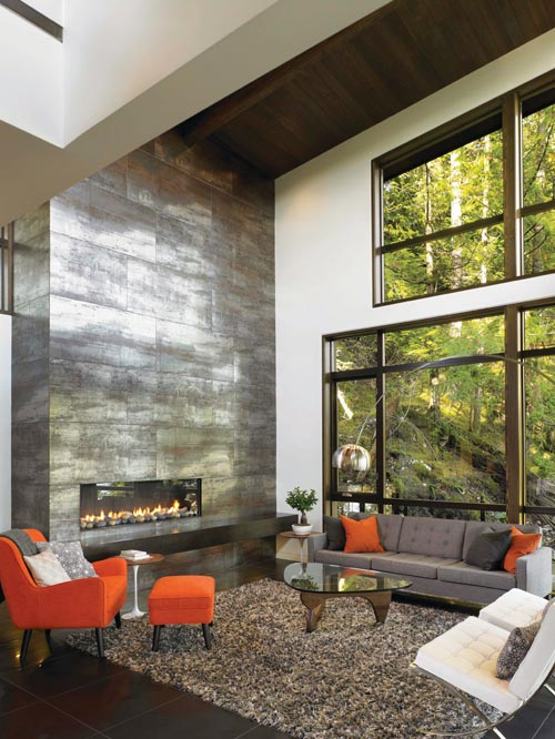 A two-storey fireplace made of ceramic tiles with metallic glaze creates a dramatic focal point for the entire home.