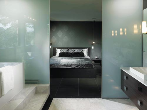 Translucent glass partitions integrate the master suite's sleeping and bathing spaces.
