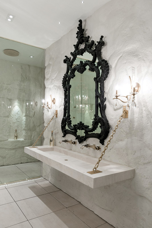 The custom gothic mirror, walls sculpted to resemble a Spanish cave, Italian limestone floor and sinks and the brushed gold finished faucets turned this en suite into an oasis.