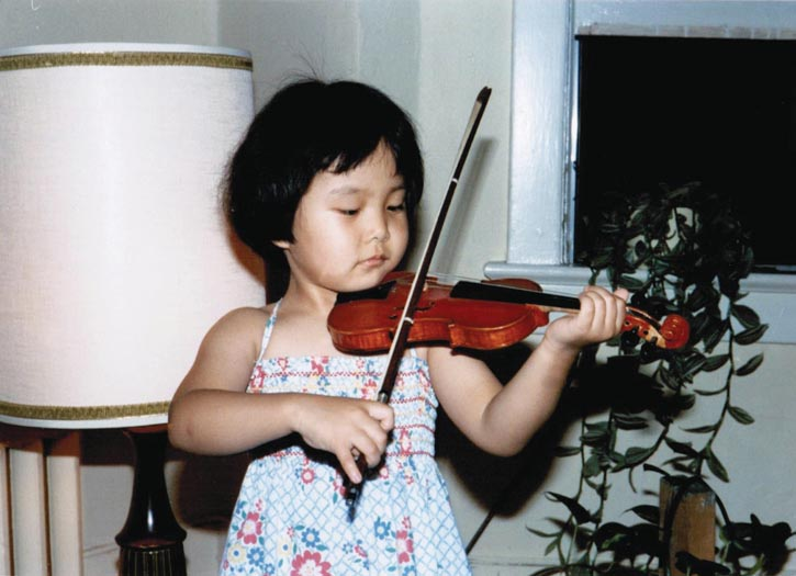 In 1981, a 4-year-old Susanne Hou practicing on a violin custom made for her by her father.
