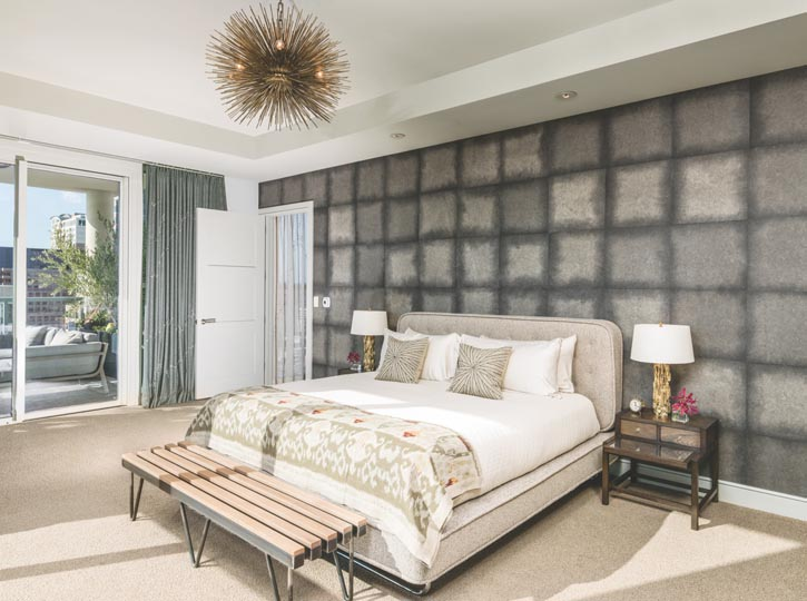 The textural wall behind the headboard is a hand-made paper by Larsen. Two 1950s German oak and stainless steel side tables flank the Cravotta bed. The Jean De Merry Lumiere Chandelier echoes the pillow pattern.