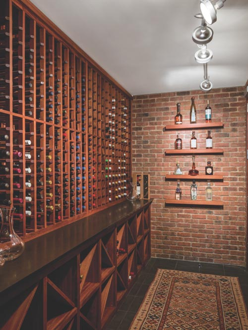 "A wine ""cellar"" was cleverly created in this Texas bachelor's apartment after lowering its ceiling to install the proper storage tools."
