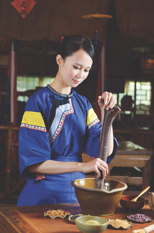 Dressed in traditional costume, a Hakka girl prepares Lei Cha soup base