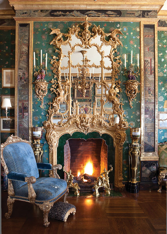 Inlaid panels of a Coromandel screen—the dark portion outlining the green wallcovering—around one of her hearths at home.