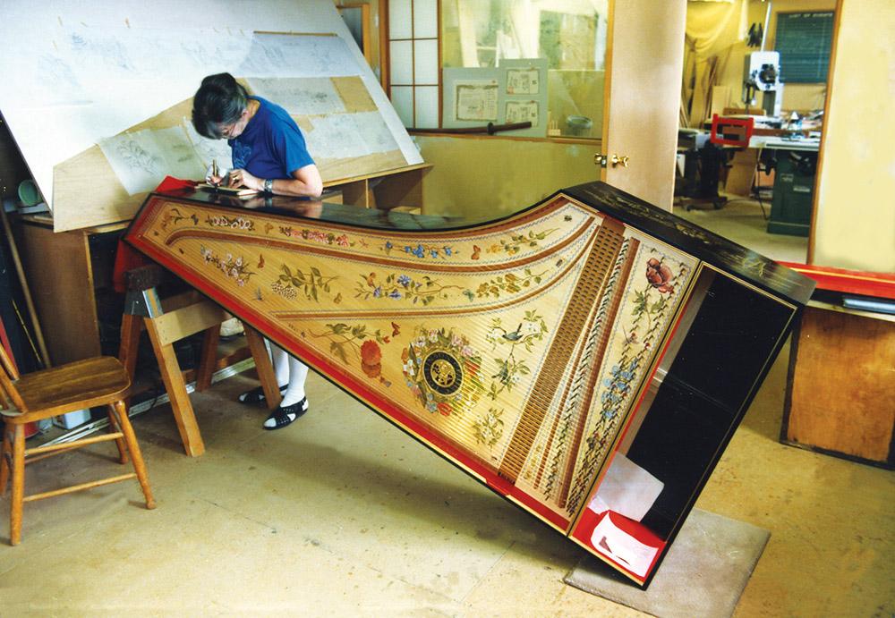 Olga Komavitch-Tomlinson applying chinoiserie decor to a harpsichord.
