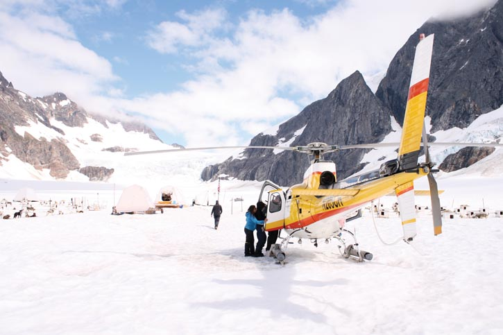 Hundreds of miles from civilization, tourists land in a helicopter on a glacier, ready to explore by dog sled.