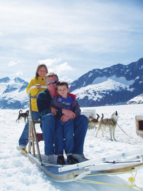 A family enjoying a half-day of dog sledding atop a glacier, the quintessential Alaskan experience.