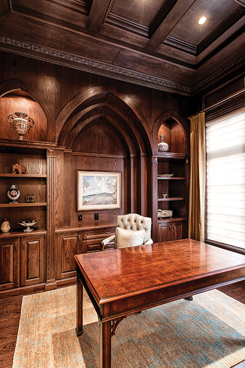 Distinctively masculine, the den is dressed with dark wood panelling and Gothic architectural elements.