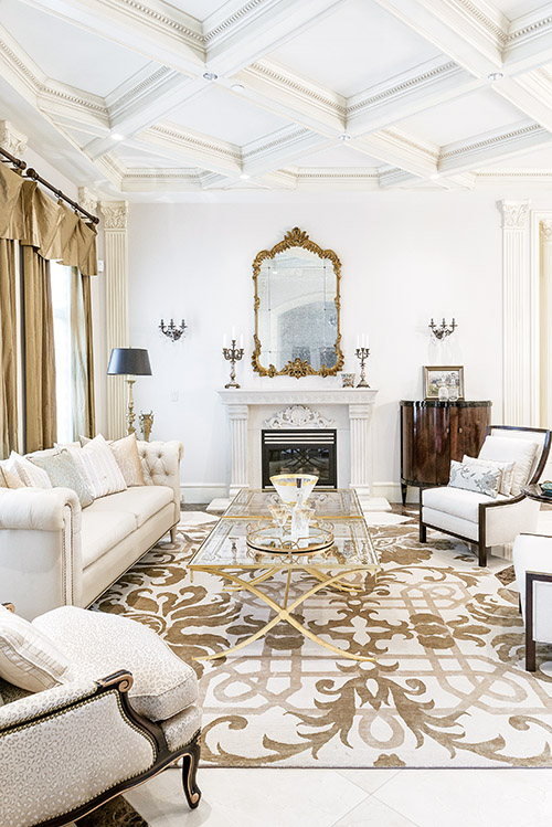 Old-world glamour is alive and gorgeous in this French-inspired living room with coffered ceilings, fluted pilasters and stunning custom coffee tables created in tandem by local artisans Mike Maca and Peter Gorman.