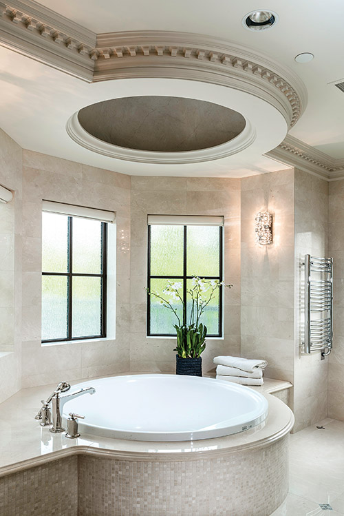 The large circular tub with ceiling silhouette is the highlight in this space. A neutral colour palette with marble accents makes the en suite timeless and elegant.
