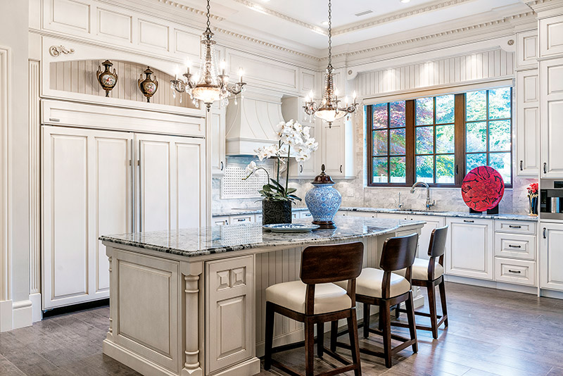 Timeless but fresh, a classic antique white kitchen is embellished with arches, moldings, custom hood surround, chandeliers, and furniture-style cabinets.