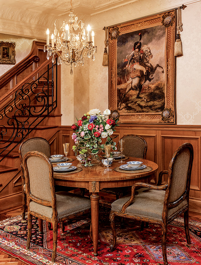 An exquisite French Louis XVI dining table with caned chairs is set for the arrival of distinguished dinner guests. The hand­milled staircase with custom balusters is a stunning collaboration by local artisans Mike Maca and Ante Anicic.