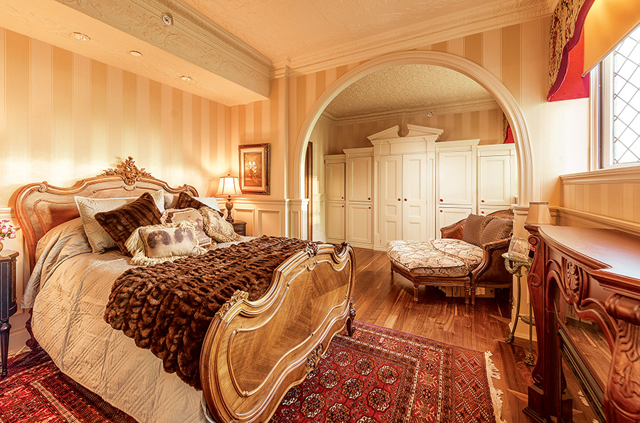 Royal dreams are induced in this restful space, replete with a French Louis XV style bed with carved feet and a Rococo cartouche to the headboard.