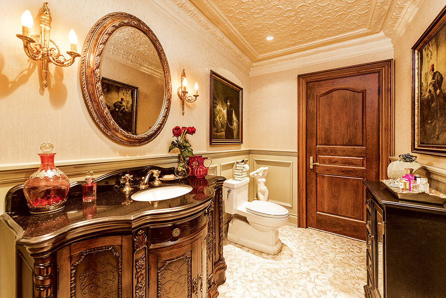 A circular mirror, antique vanity with decorative baroque veneer, and whimsical sconces adorn this bathroom like jewellery.
