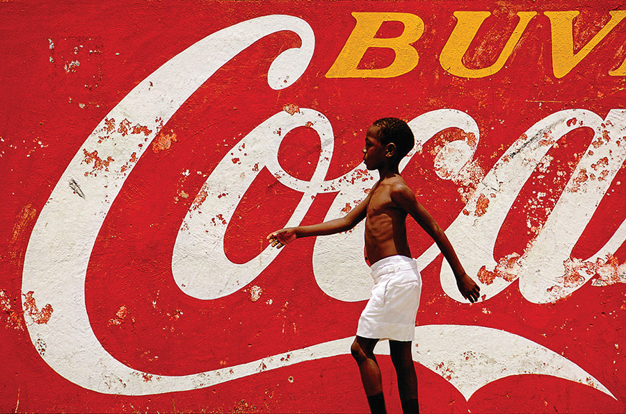 """Coca Kid"" is considered Eric Meola's most famous image — an intensely graphic bold wash of colour that came together after hours waiting in one spot on the sidewalk in Port-au-Prince, Haiti."
