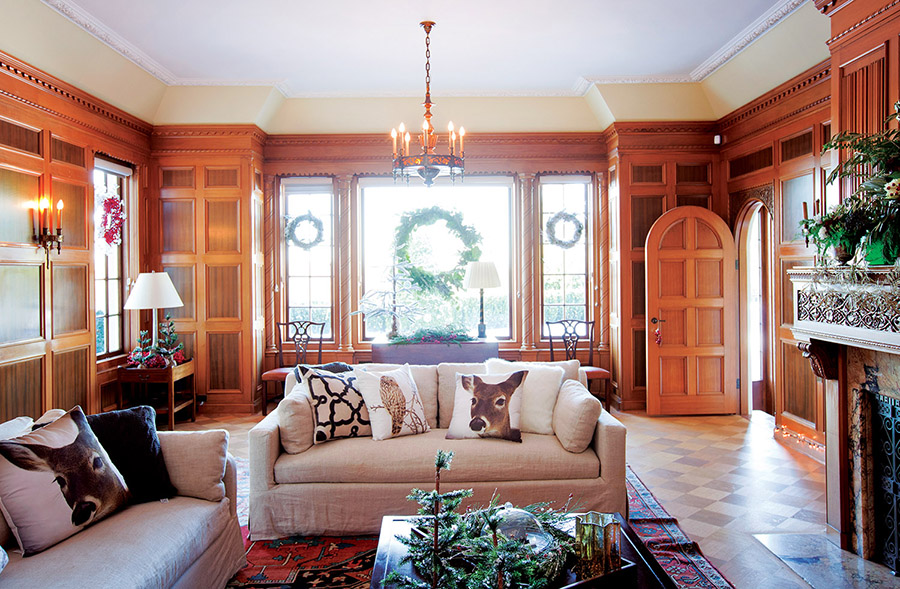 "Faux-fur throws, evergreen boughs and reindeer pillows bring the ""Into the Woods"" theme to life in this sophisticated family room with rosewood-panelled walls."