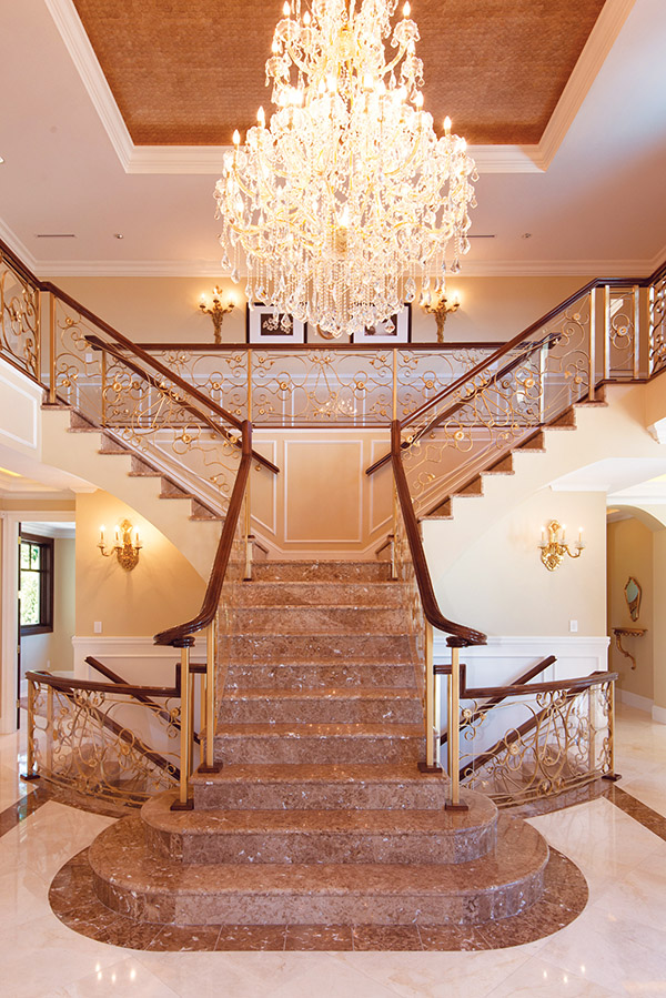 Designer David Christopher applied his artistic finesse to the creation of this opulent staircase, inspired by a European castle and brought to life with hand-forged gold railings and marble steps.