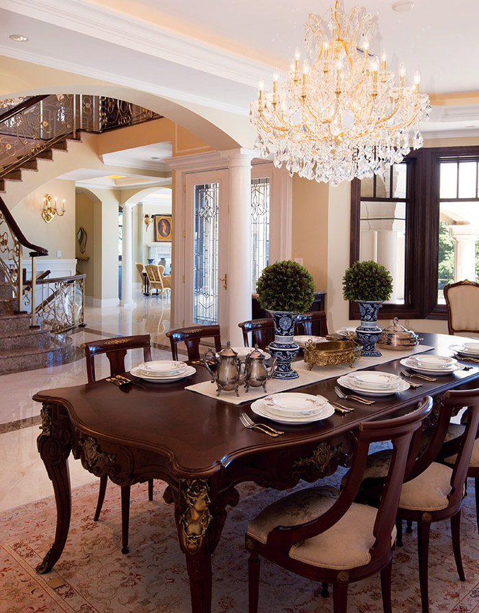 An open floor plan provides a flowing, continuous feeling, from the grand entry to the lavish dining room, with its crystal chandelier and gold Versace light fixtures.