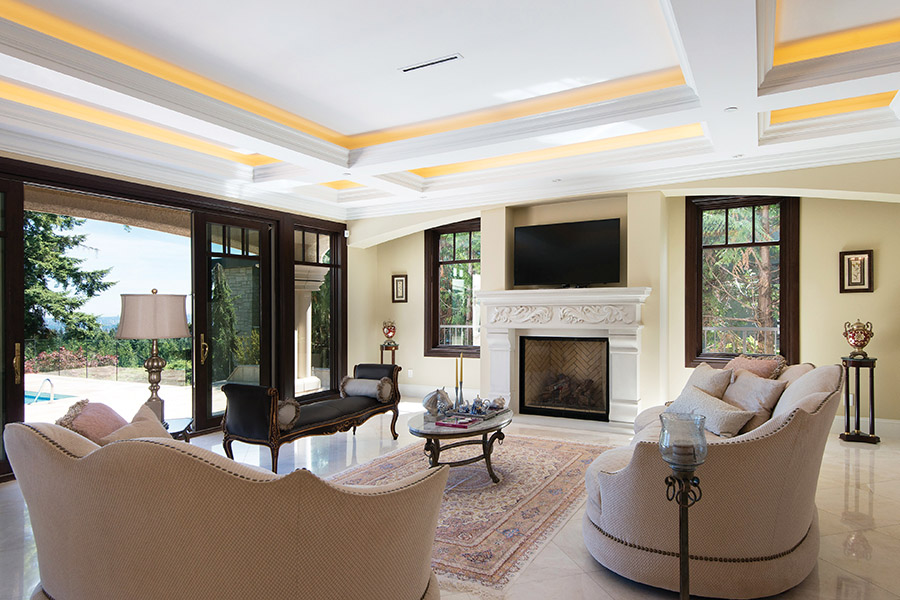 From the coved ceiling, modern LED lighting casts a golden glow on the elegant sitting room, furnished with regal neoclassical furniture — many pieces incorporating gold leaf.