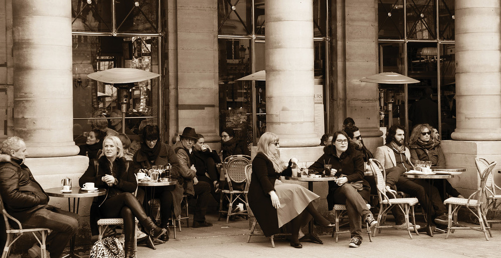 Parisians and tourists sit on the terrace of Le Nemours cafe. This popular cafe, an ideal place for people watching, is located near Palais Royal and Comedie Francaise.