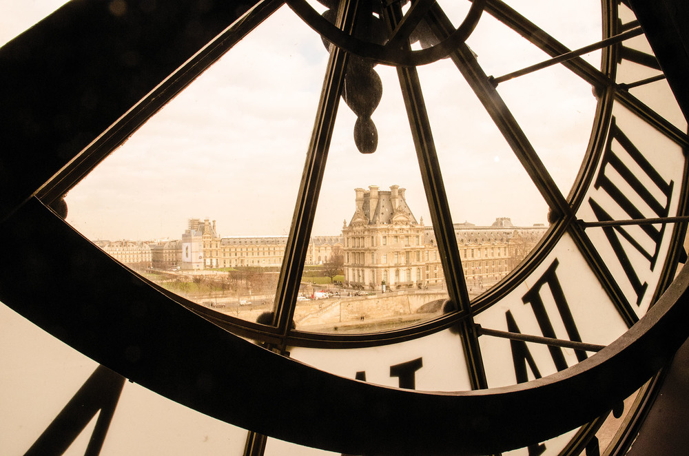 The Louvre Museum seen through the clock window of museum d'Orsay, in Paris