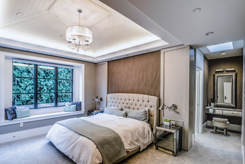 The master bedroom is Eric and Janey's sanctuary, striking a fine balance with white-washed oak wall panels, plush wall coverings and a makeup vanity.