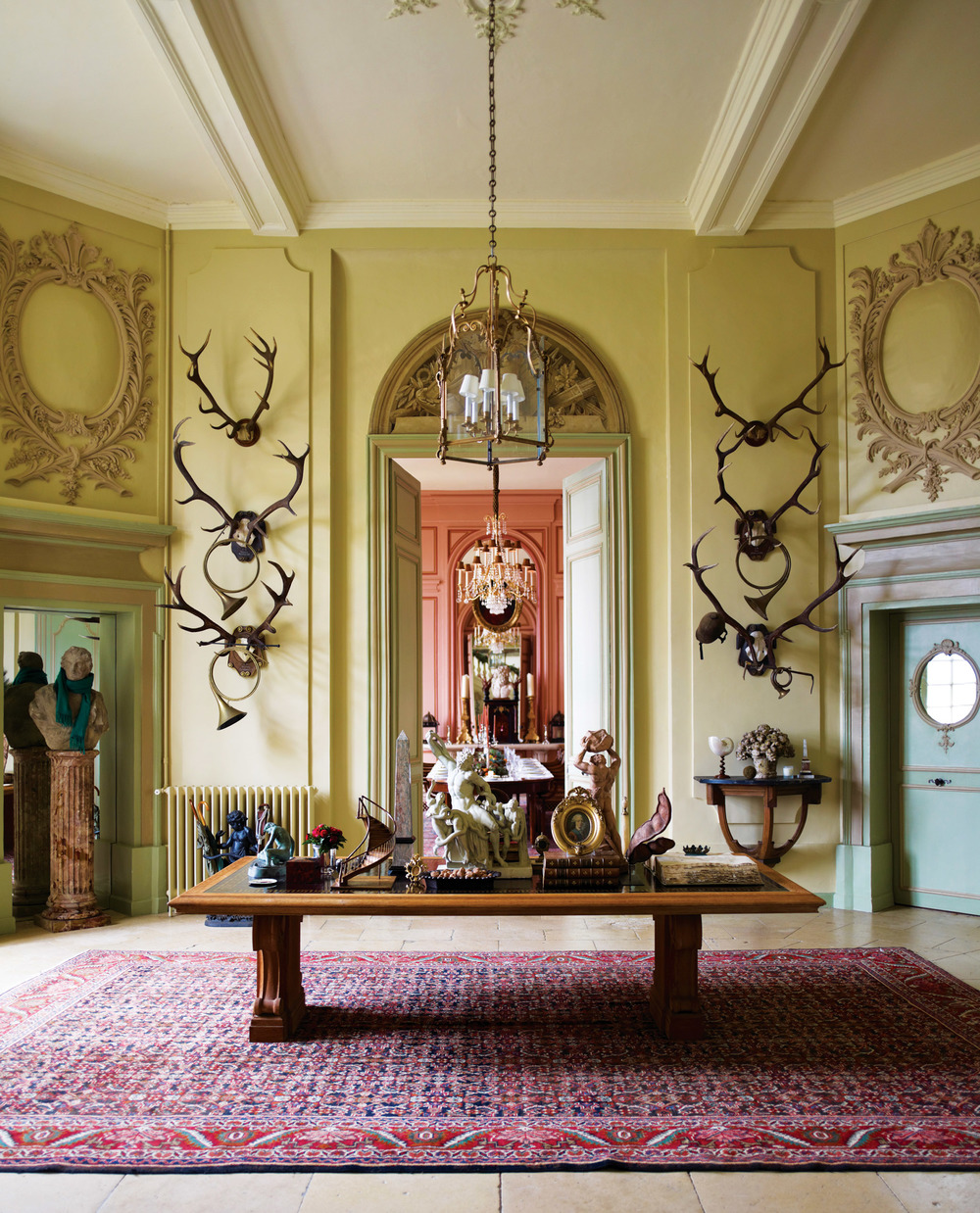 Corrigan's classical tastes walk hand-in-hand with antique treasure hunting, with two of his dearest fids being a massive 1940s table by Jean-Charles Moreaux in his French chateau, and a c. 1975 mahogany cabinet depicting, in porcelain, 32 great Greek gods and philosophers, in his Los Angeles study.