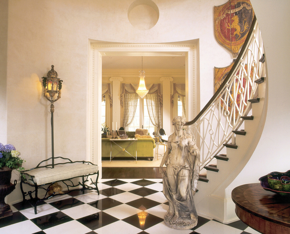 A neutral foyer, finished with a statue from the Bill Blass estate, leads the eyes towards the inviting living room.