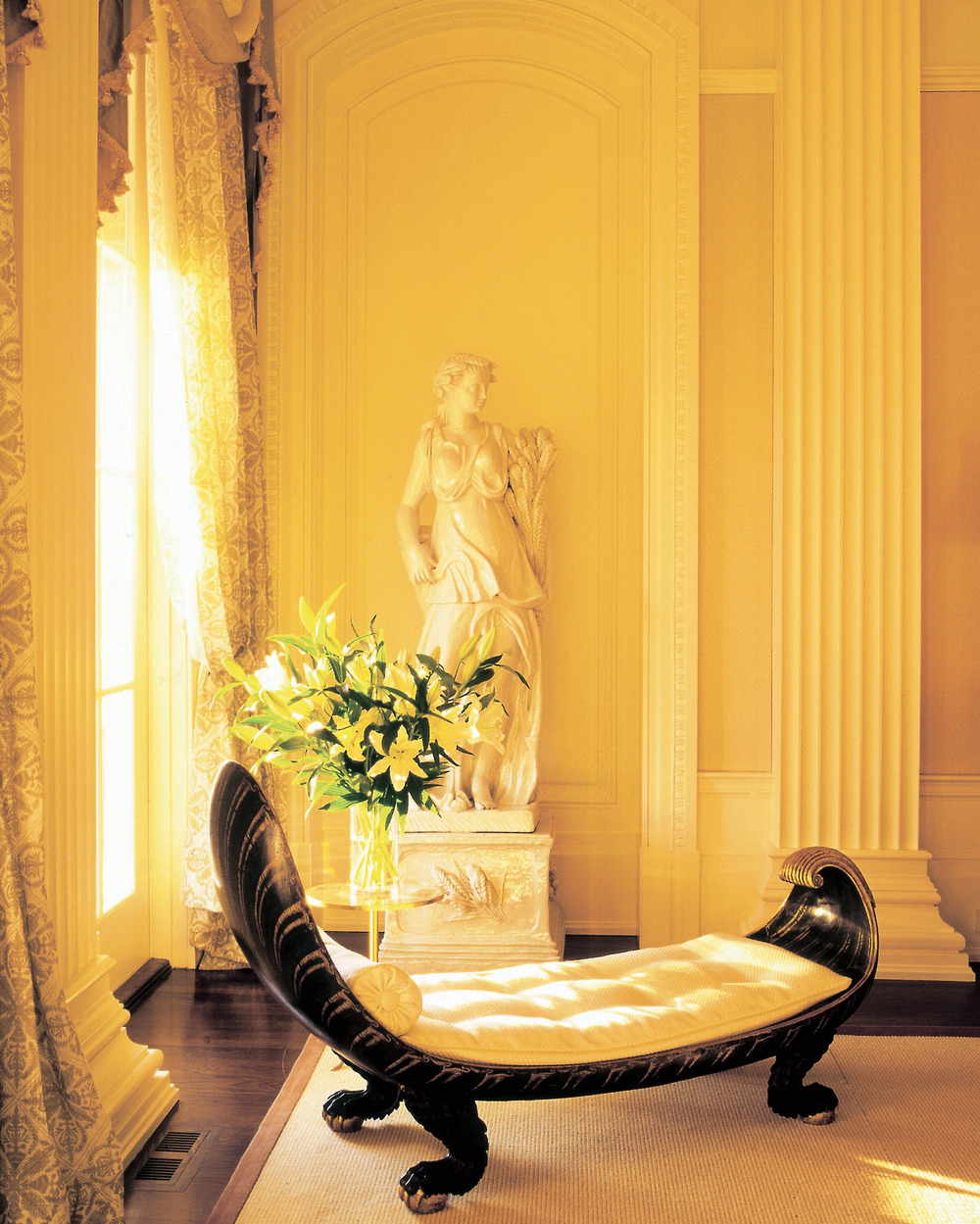 """An antique, shell-shaped Italian chaise and 18th-century statue (""""Summer"""" from the four seasons statues) pose near the French doors of the living room."""