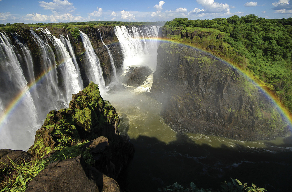 A rainbow casts over Victoria Falls in Zimbabwe. The falls and the surrounding area are a World Heritage Site.Jixin YU / Sutterstock.com