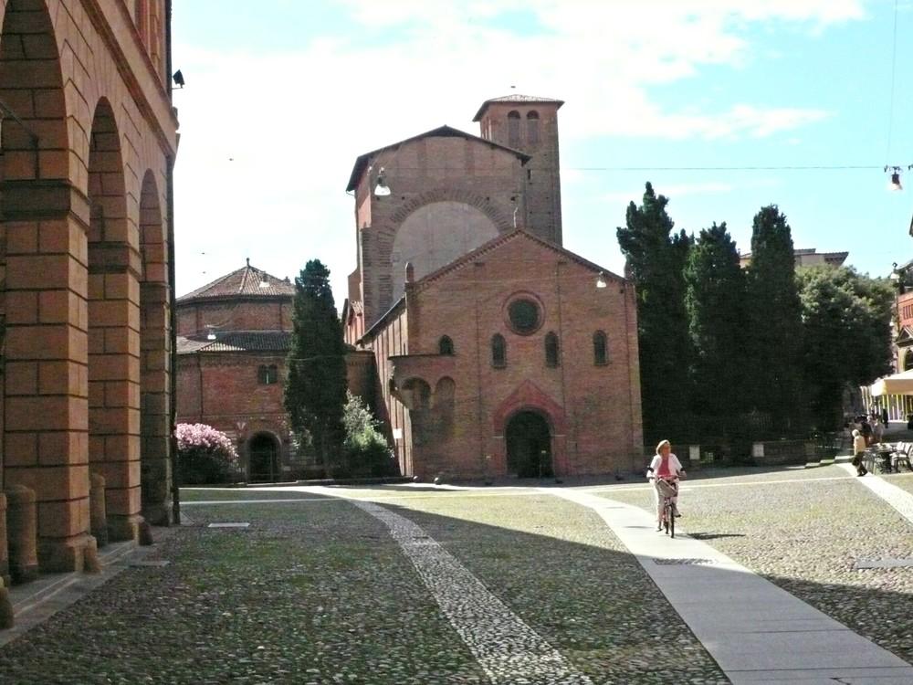 A woman rides a bike through Piazza Santo Stefano. (Ben Maloney)