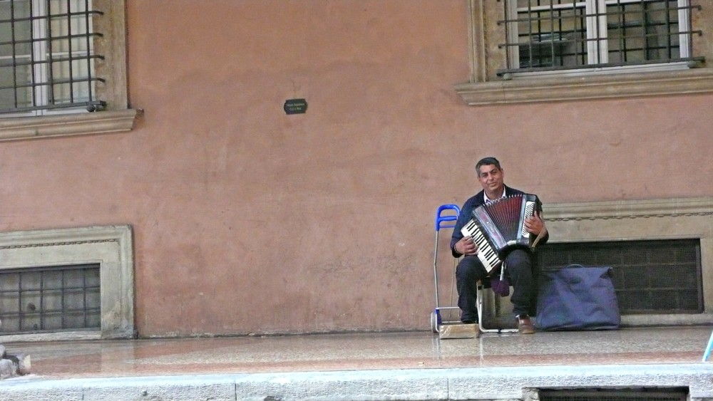 A man plays music on the street in Bologna's center. (Ben Maloney)