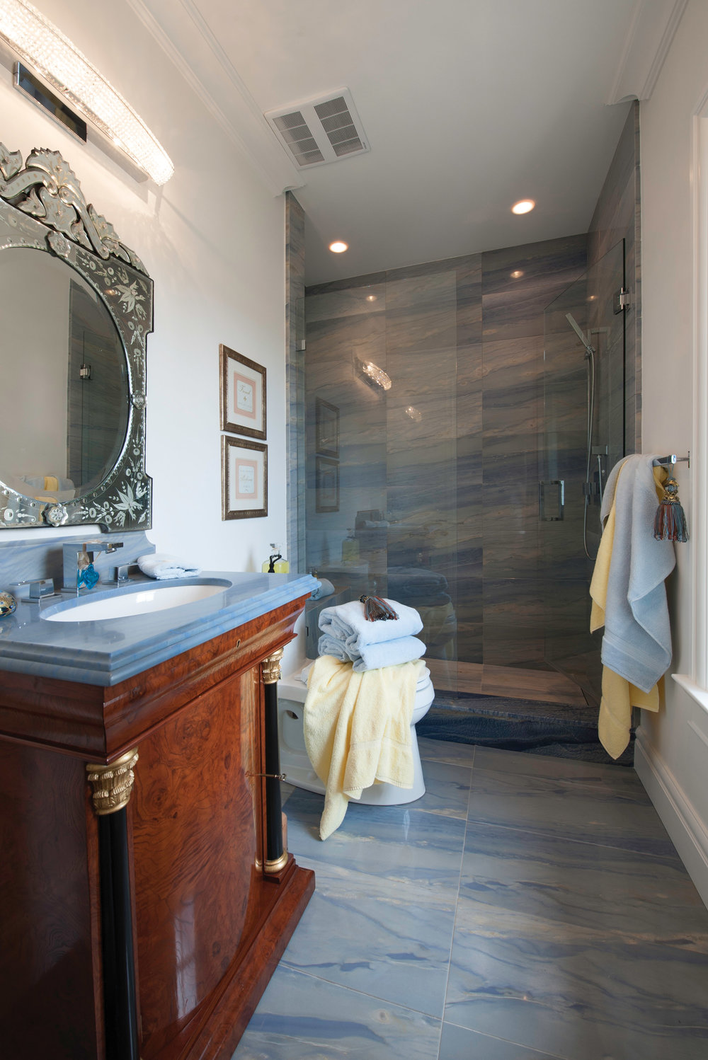 An antique buffet is repurposed as a bathroom vanity and topped with rare, highly prized blue granite.