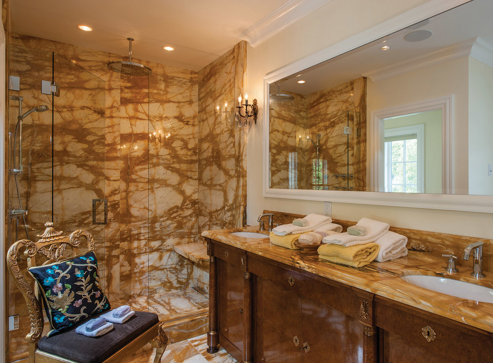The master bath features bold Giallo di Siena marble, an ancient yellow stone netted with fine black veins.