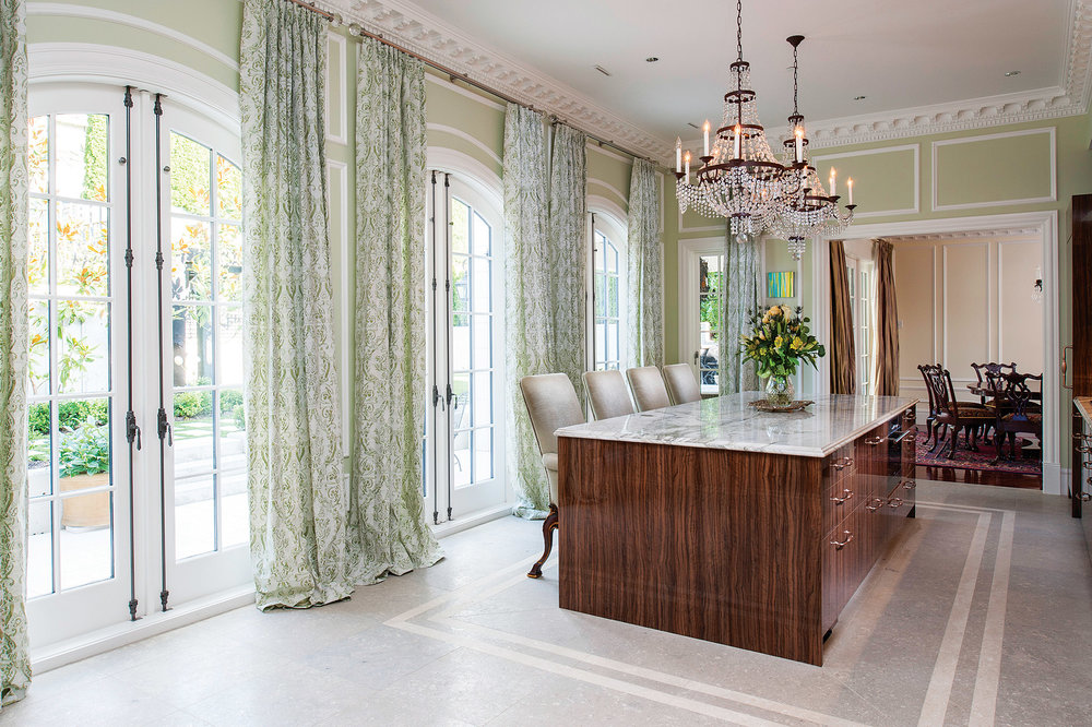 "The showpiece kitchen is anchored by a massive Carrara marble-top island. Cabinets made of lustrous Tuscan olive wood are illuminated by French Empire crystal chandeliers. Fortuny fabrics from Venice in a signature ""Sévigné"" lime green and old ivory pattern dress the French doors leading out to the vineyard garden."