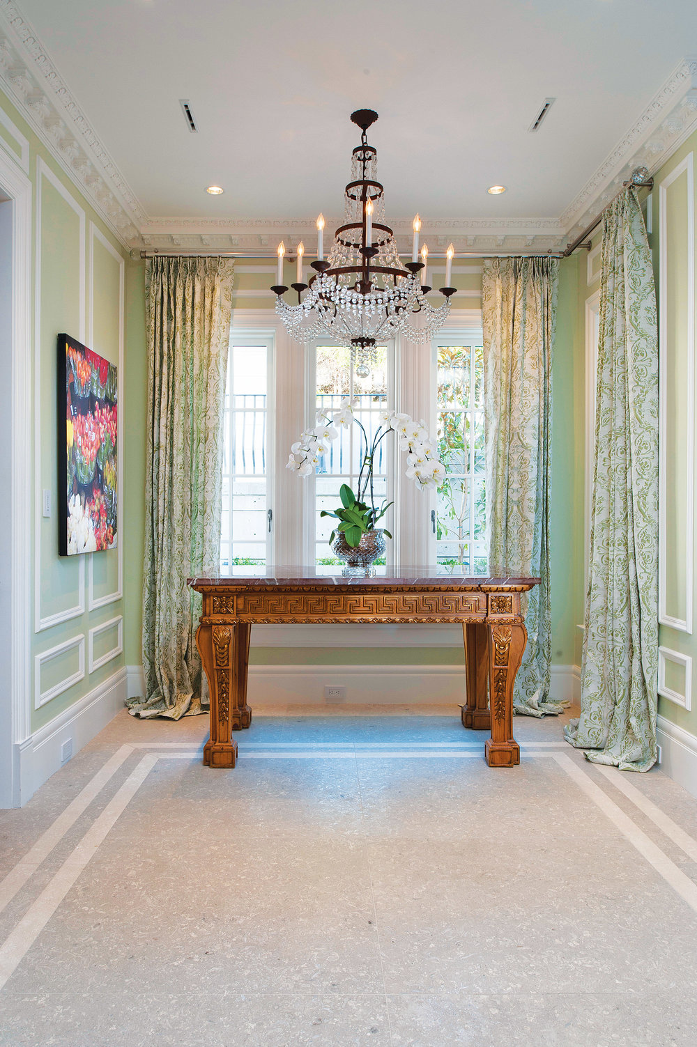 Classic ornamentations like delicate picture-frame molding on the walls and intricate crown molding are paired with a William Kent table and Fortuny curtains.