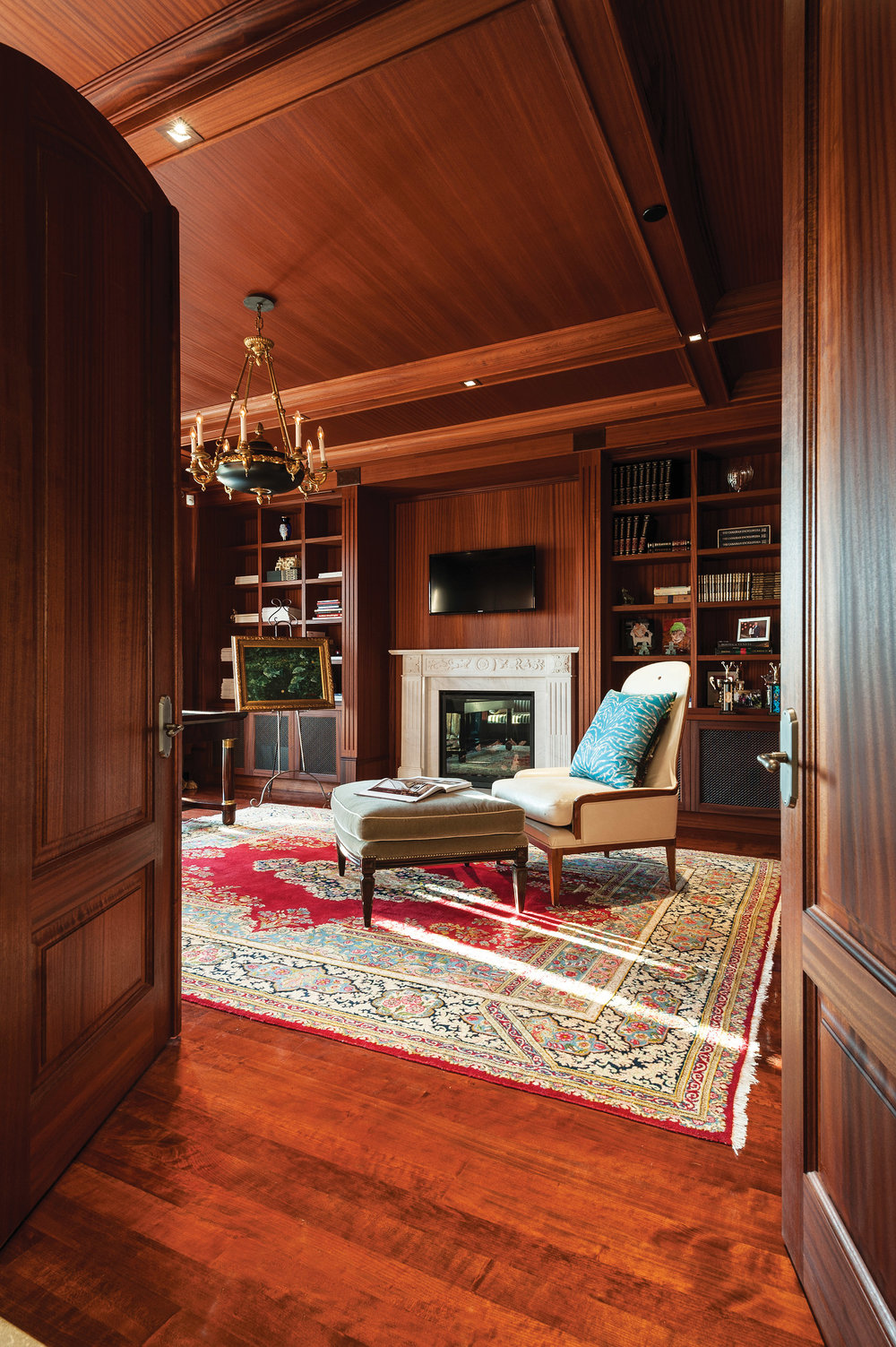 Library walls and coffered ceiling are sheathed in mahogany panels. Furnishings include Le Moulin Chair in bone leather and an Italian Louis XVI chandelier.
