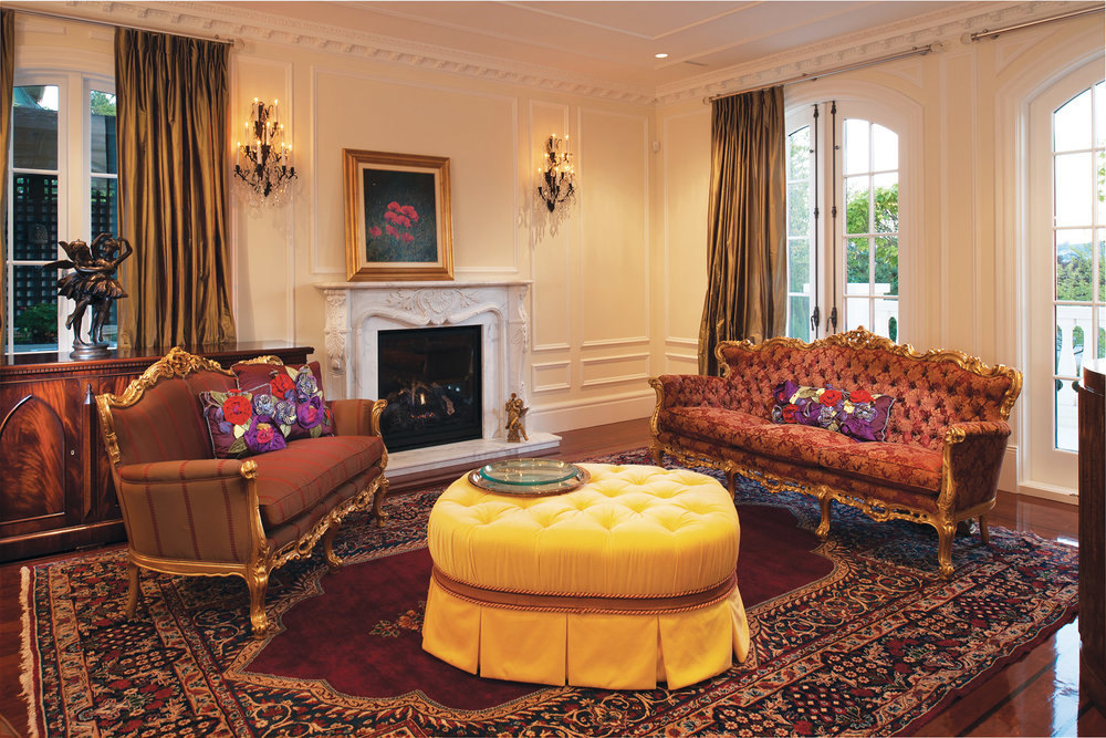 Exuding French formality with its royal settees and hand-carved marble fireplace, the living room displays Fusco Zanatta's favourite piece, a custom yellow tuft ottoman.