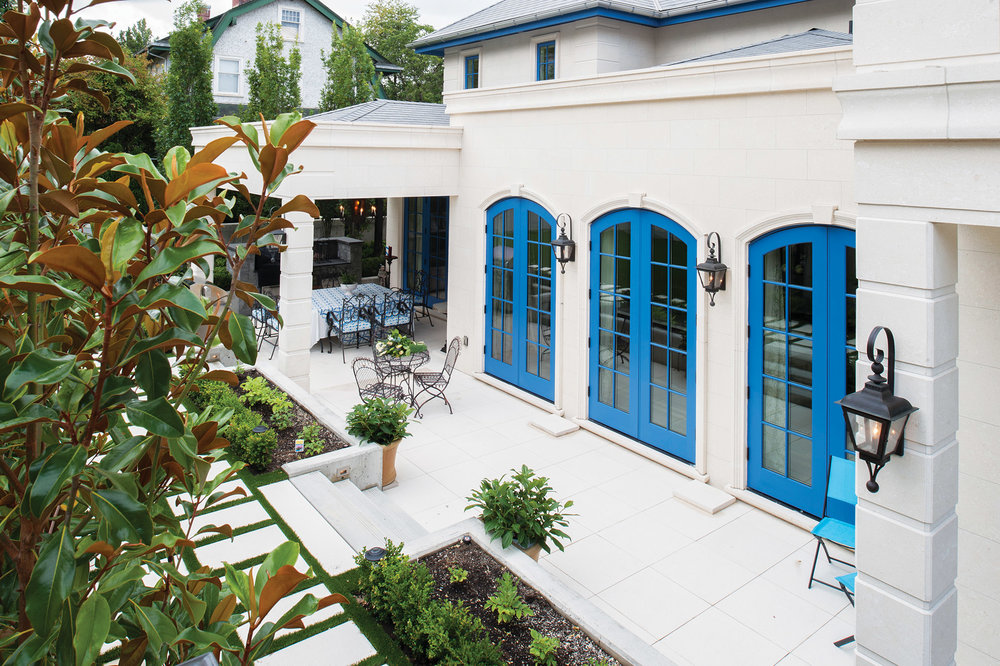 Ville de Shaughnessy has impeccable old-world panache inspired by its owners' travels to the Mediterranean. Windows trimmed in French blue pop against the honey-hued Italian limestone.