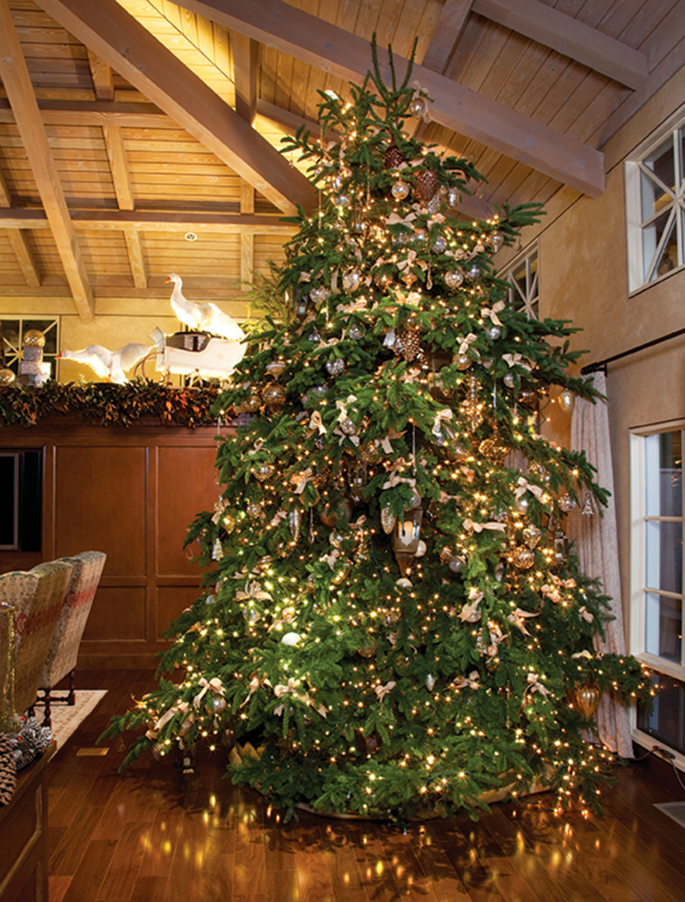 A 23-foot-high noble fir complements the high ceilings of the family room. The tree's ornaments are made of mercury glass — double-walled with silver in between — to reflect the light around the room.