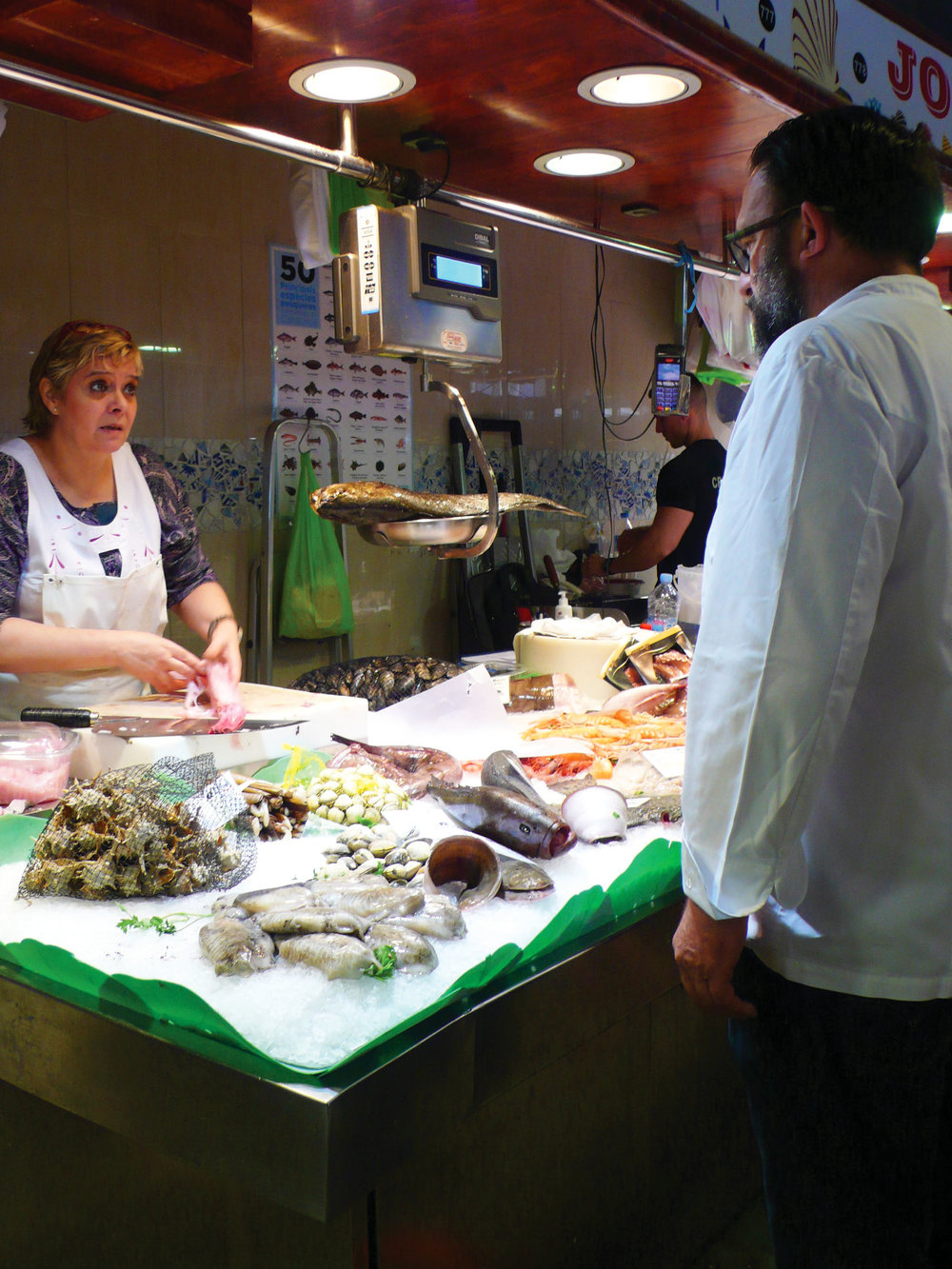 Chef Oscar Manresa talks to the fish expert at La Boqueria marketplace. Photo by Ben Maloney.
