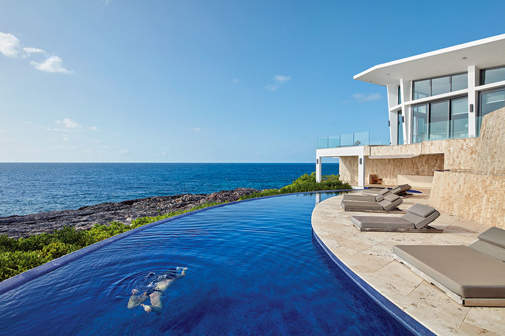 The graceful arc of the infinity pool echoes the arc of the shoreline, creating a seamless experience of sea and sky. The intense azure pool tiles are imported from Turkey, and match the colour of the ocean beyond.