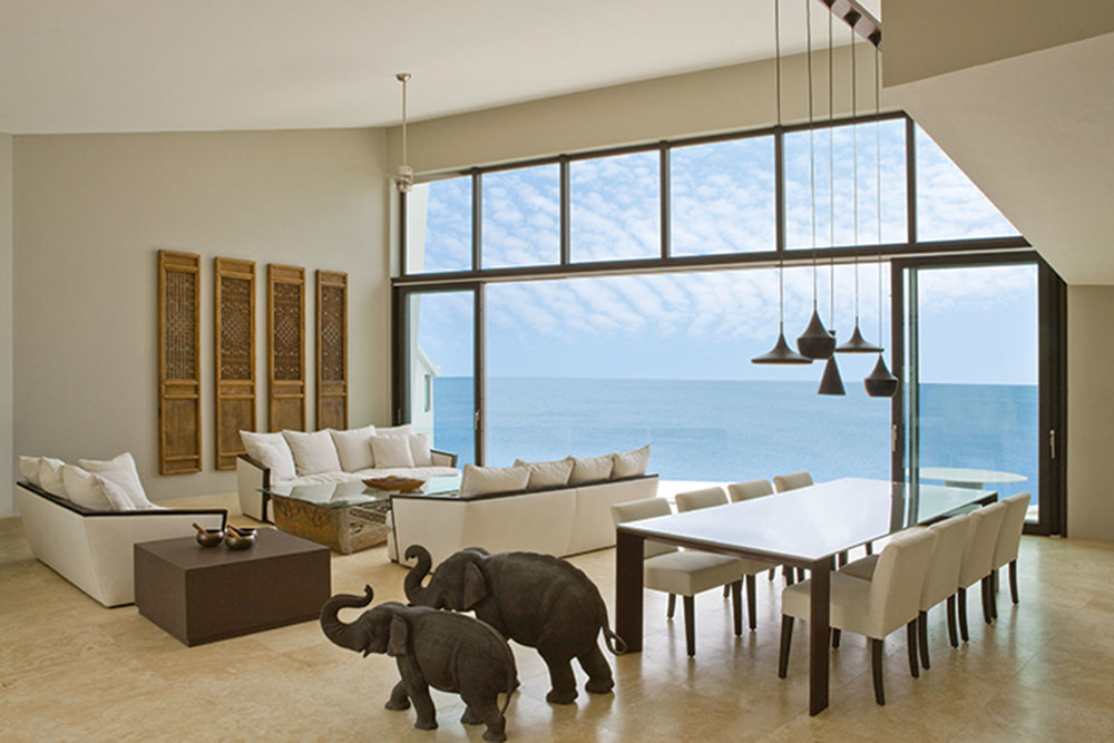 Fifteen-foot high ceilings vault slowly towards the floor-to-ceiling windows which create a breathtaking frame for the view of the ocean. Balinese carved elephants add a bit of personality and a subtle nod to the homeowners' love of travel.