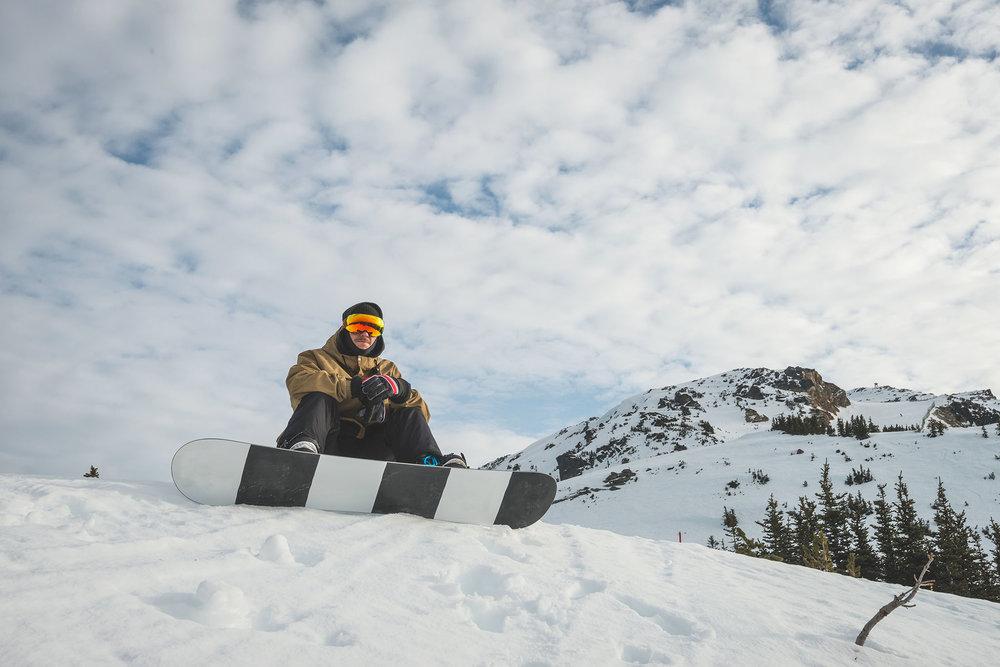 A snowboarder takes a break mid-mountain.John Crux / shutterstock.com