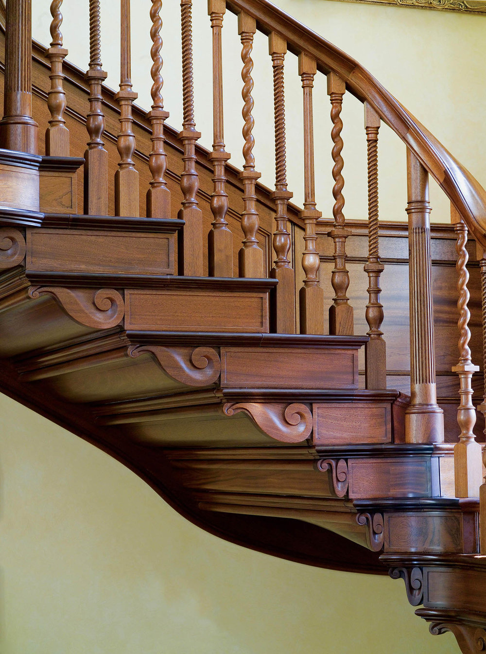 "Hand-carved ""waves"" dance across the bottom of grand foyer's mahogany staircase."