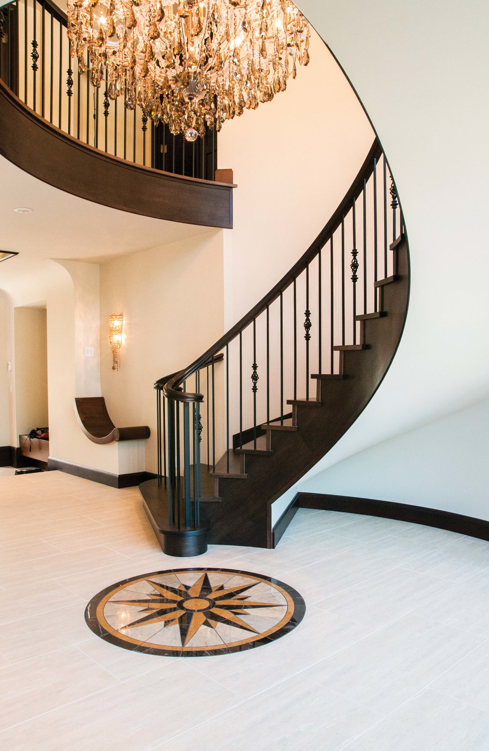 Flowing curves of entry stairs, bench seat, and landing, along with inlaid floor medallion, work together to form a graceful composition that encompasses the brilliant Schonbek chandelier.